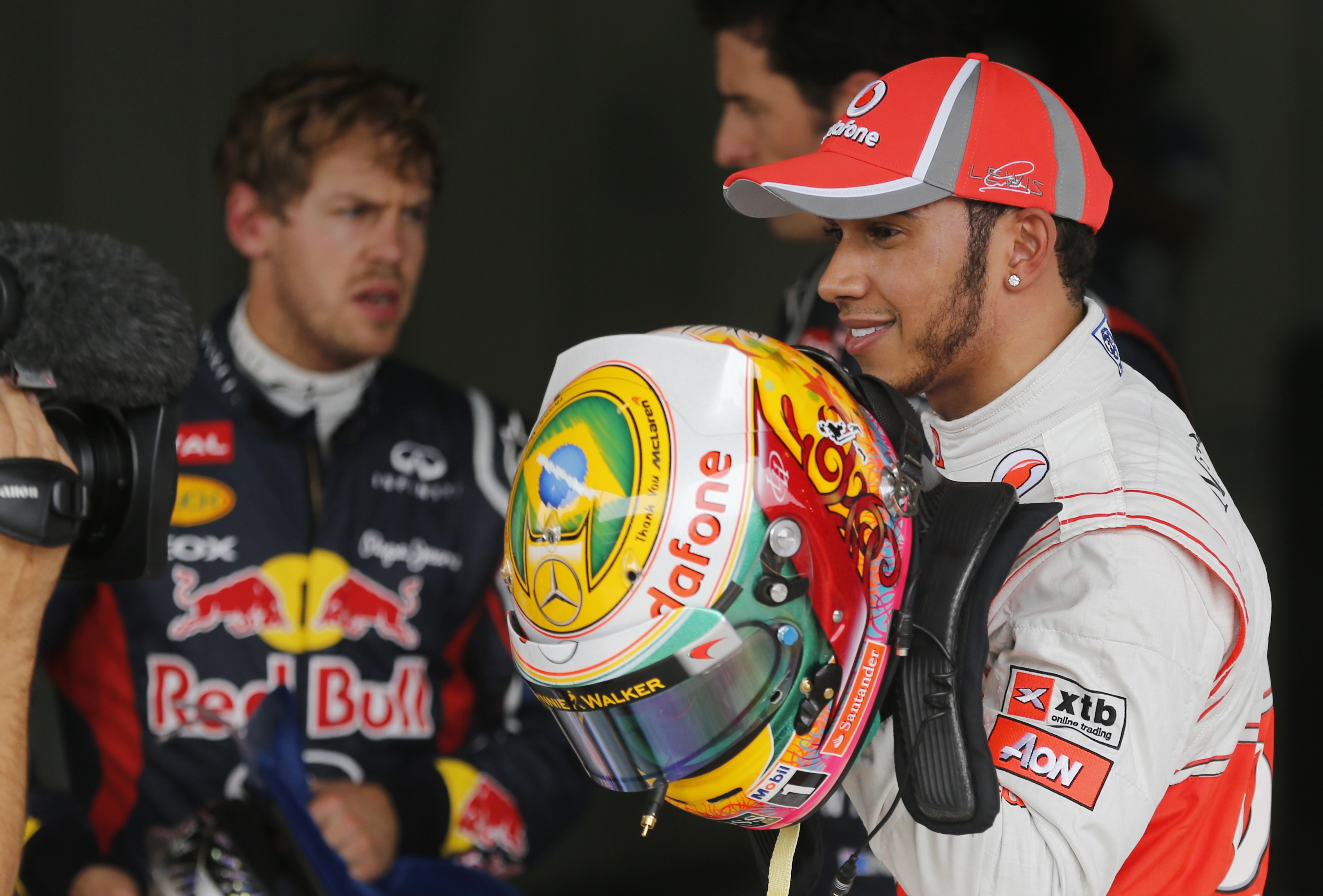 Fastest qualifier Lewis Hamilton shows off his Brazilian flag helmet on November 24, 2012