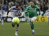 Lyon's Bafe Gomis challenges for the ball with Saint-Etienne's Loic Perrin on December 9, 2012