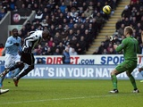 Newcastle striker Demba Ba heads the ball past Joe Hart on December 15, 2012