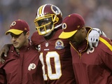 Robert Griffin III of the Washington Redskins is helped off the field on December 9, 2012