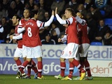 Arsenal players congratulate Lukas Podolski after he opened the scoring against Reading on December 17, 2012