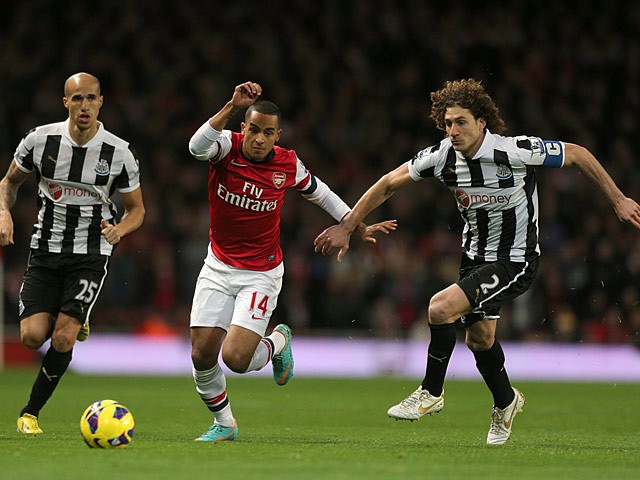 Theo Walcott and Fabricio Coloccini battle for the ball on December 29, 2012
