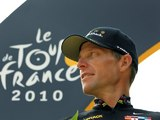 Lance Armstrong in front of a Tour de France brand board in 2010