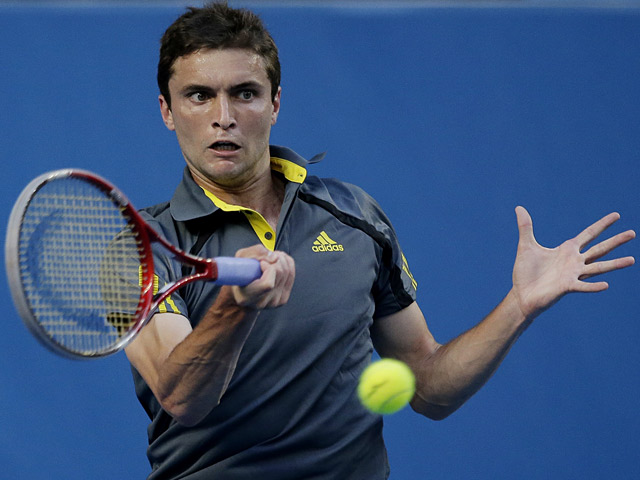 Gilles Simon hits a return to Gael Monfils during their third round match at the Australian Open on January 19, 2013