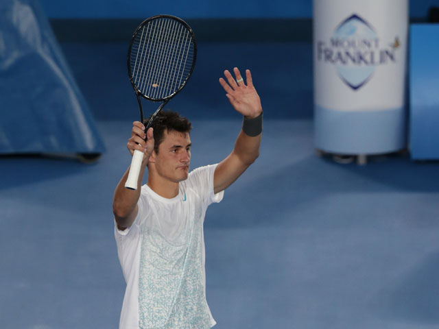 Bernard Tomic from Australia waves to the crowd after defeating Leonardo Mayer in the first round at the Australian Open tennis championship on January 15, 2013