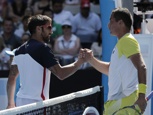 Serbia's Janko Tipsarevic and Nicolas Almagro shake hands after Tipsarevic retired injured in the fourth round of the Australian Open tennis championship on January 20, 2013