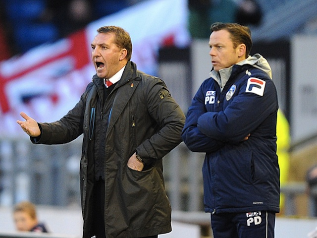 Opposing managers Brendan Rodgers and Paul Dickov stand on the touchline during the game between Oldham and Liverpool on January 27, 2013