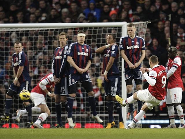 Lukas Podolski scores a deflected free-kick against Stoke on February 2, 2013