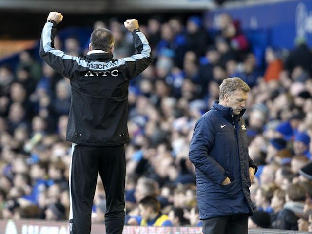 Villa boss Paul Lambert celebrates his side taking the lead against Everton, as opposing manager David Moyes walks away on February 2, 2013