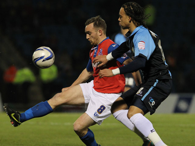 Gillingham's Charlie Lee (left) is challenged by Wycombe Wanderers' Charles Dunne during their side's match on February 4, 2013