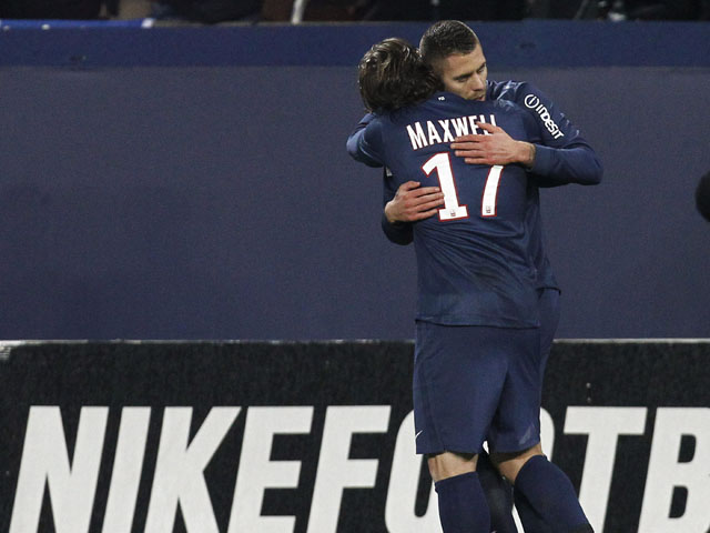 Paris Saint Germain's midfielder Jeremy Menez is congratulated after scoring by his teammate Maxwell on February 8, 2013