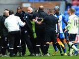 Newcastle coach John Carver is held back after having words with Wigan's Graham Barrow on March 17, 2013