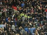 Trouble breaks out in the stands between Milwall fans and police during the match between Wigan and Millwall on April 13, 2013