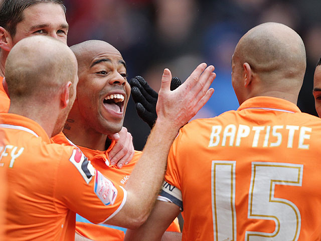 Blackpool's Ludovic Sylvestre is mobbed by teammates after scoring the winning goal against Burnley on April 13, 2013