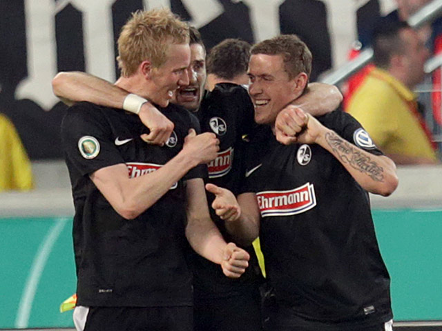 Freiburg's Jan Rosenthal is congratulated by teammates after scoring the equaliser against Stuttgart on April 17, 2013