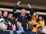 Hull City's manager Steve Bruce celebrates in the stands after his side sealed promotion to the Premier League on May 4, 2013