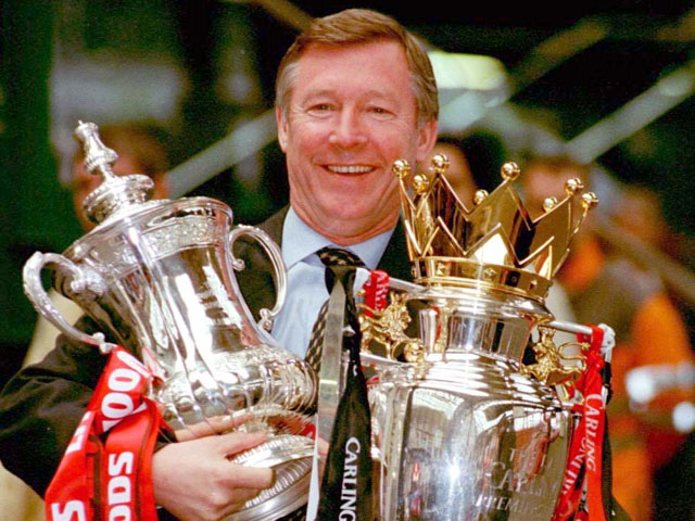 Manchester United manager Alex Ferguson proudly displays the FA Cup and Premier League trophies