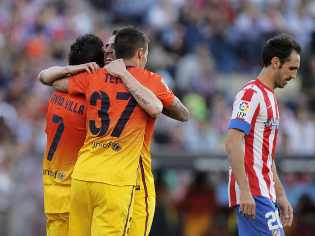 FC Barcelona players celebrate after Atletico Madrid's Gabi Fernandez scores an own goal on May 12, 2013