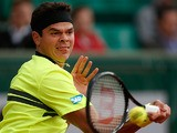 Milos Raonic returns the ball to Michael Llodra during their second round match of the French Open on May 29, 2013