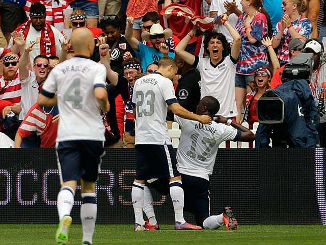 USA's Jozy Altidore celebrates with team mate Fabian Johnson and fans after scoring the opening goal against Germany in a friendly match on June 2, 2013