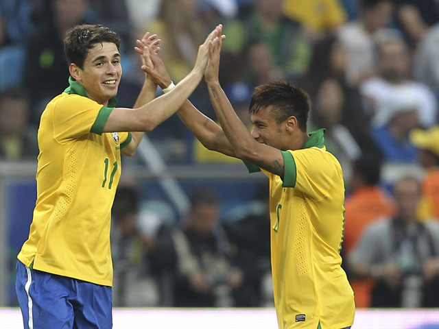Brazil's Oscar celebrates his goal with teammate Neymar during their friendly soccer game against France on June 9, 2013