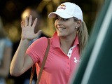 Skier Lindsey Vonn waves after watching Tiger Woods during the second round of the Masters on April 12, 2013