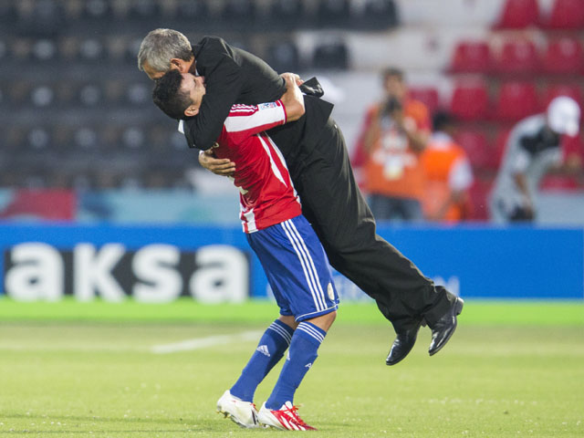 Paraguay's Miller Mareco lifts up Paraguay's head coach Victor Genes after the Under-20 World Cup Group D soccer match between Mexico and Paraguay on June 25, 2013