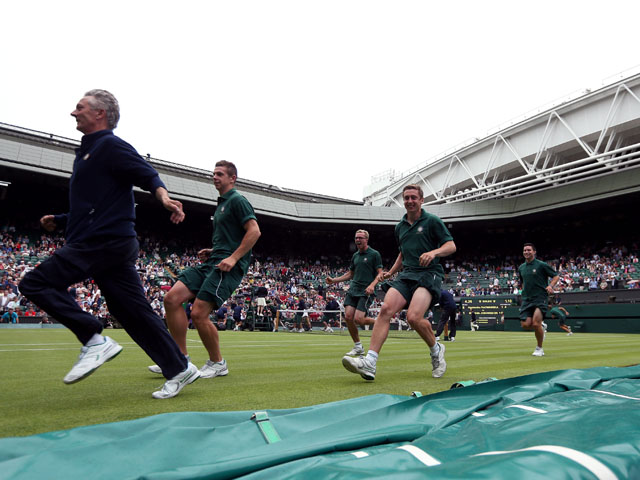 Groundstaff race to put the covers on centre court as rain stops play