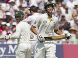 Australia's Ashton Agar smiles as he passes fellow batsman Phillip Hughes as the pair surpass the record for a 10th wicket Test partnership on day two of the first Ashes Test on July 11, 2013