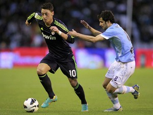Celta's Alex Lopez tries to tackle Mesut Ozil during the La Liga match against Real Madrid on March 10, 2013