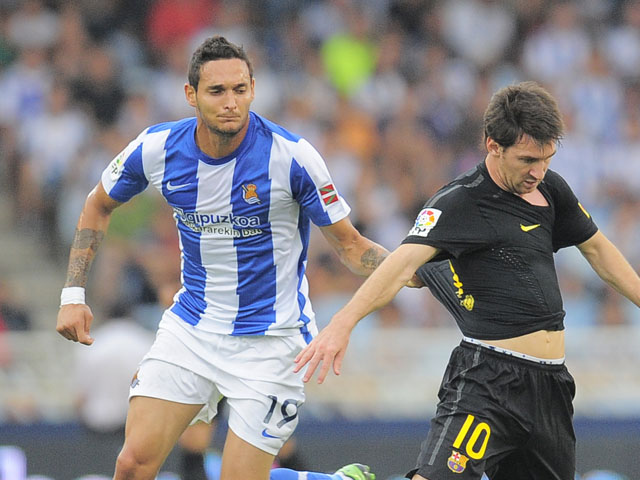 Real Sociedad's Liassine Cadamuro tangles with Barcelona's Lionel Messi during the La Liga match on September 10, 2011