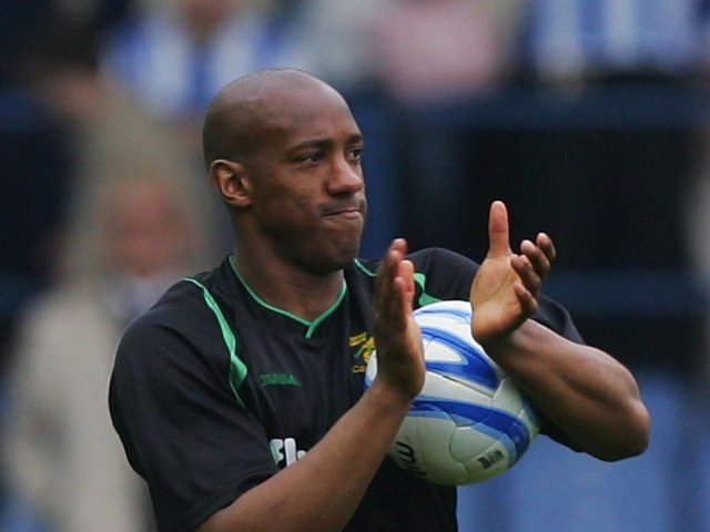Dion Dublin applauds the travelling Norwich City fans.