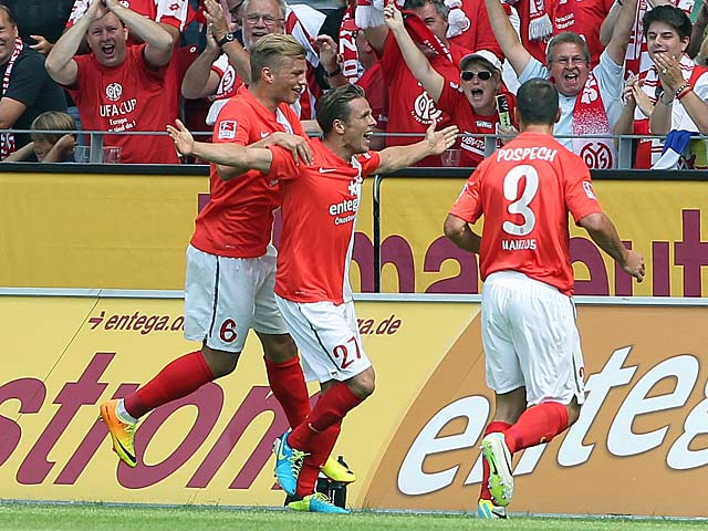 Mainz' Nicolai Mueller is congratulated by team mates after scoring the opening goal against Stuttgart on August 11, 2013
