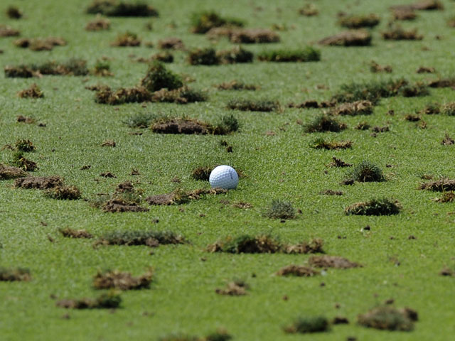 A golf ball sits among the divots on the driving range during a practice round on August 10, 2009