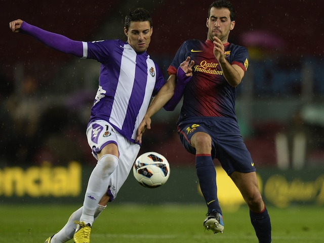 Real Valladolid's Oscar Gonzalez battles with Sergio Busquets of Barcelona on May 19, 2013