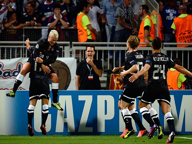 Real Sociedad's Antoine Griezmann is congratulated by team mates after scoring the opening goal against Lyon on August 20, 2013
