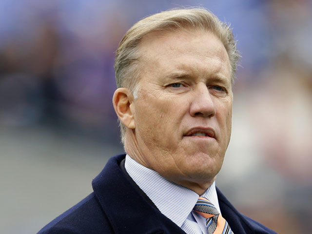 John Elway, executive vice president of football operations of the Denver Broncos watches the team warm up before the start of the Broncos game against the Baltimore Ravens at M&T Bank Stadium on December 16, 2012
