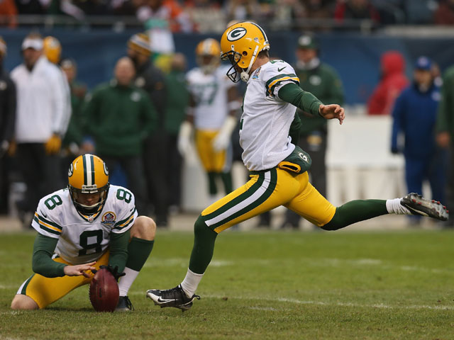 Mason Crosby #2 of the Green Bay Packers attempts a field goal out of the hold of Tim Masthay #8 at Soldier Field on December 16, 2012