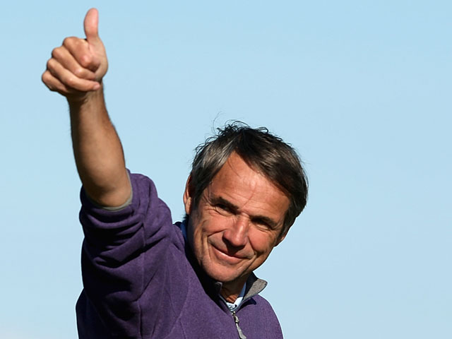 Football pundit Alan Hansen waves to Ruud Gullit and Jamie Redknapp on the stands on the 17th green during the final round of The Alfred Dunhill Links Championship at The Old Course on October 7, 2012