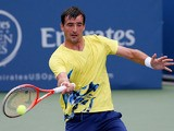Ivan Dodig of Croatia returns a forehand to Lleyton Hewitt of Australia during the BB&T Atlanta Open in Atlantic Station on July 26, 2013