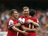 Arsenal's Per Mertesackeris congratulated by teammates Aaron Ramsey and Mesut Ozil after scoring his team's second goal against Stoke during their Premier League match on September 22, 2013
