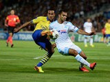 Arsenal's Theo Walcott and Marseille's Jeromy Morel battle for the ball during their Champions League group match on September 18, 2013