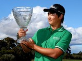 Jin Jeong of Korea holds aloft the winners trophy after defeating Ross Fisher of England on a play-off hole to win the tournament during day four of the Perth International at Lake Karrinyup Country Club on October 20, 2013