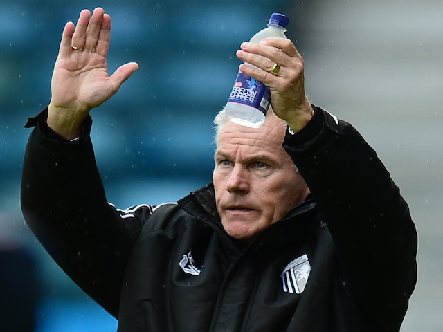 Peter Taylor, manager of Gillingham waves to the fans as he walks onto the pitch before the Sky Bet League One match between Gillingham and Preston North End on October 19, 2013