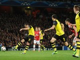 Henrik Mkhitaryan of Borussia Dortmund scores the first goal during the UEFA Champions League Group F match between Arsenal and Borussia Dortmund at Emirates Stadium on October 22, 2013