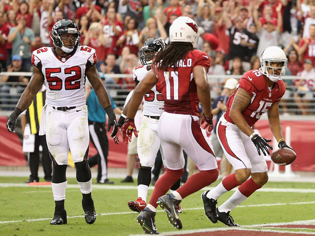 Wide receiver Michael Floyd #15 of the Arizona Cardinals looks over to Larry Fitzgerald #11 after catching a 15 yard touchdown reception against the Atlanta Falcons during the second quarter of the NFL game at the University of Phoenix Stadium on October