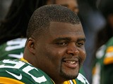 B.J. Raji #90 of the Green Bay Packers watches from the bench as his teammates take on the Arizona Cardinals at Lambeau Field on August 9, 2013