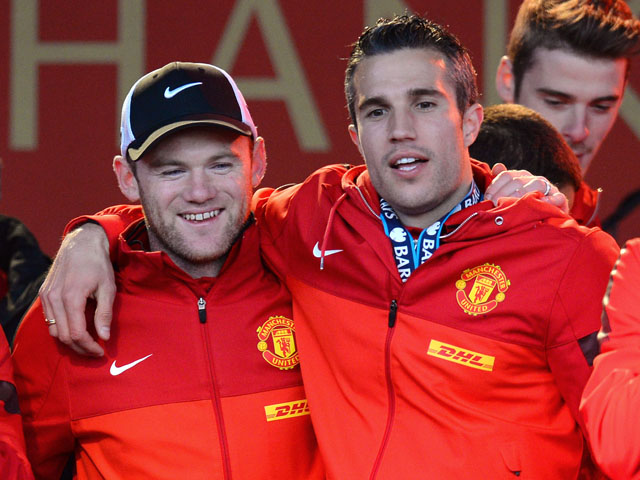 Manchester United's Dutch striker Robin van Persie and English striker Wayne Rooney celebrate on stage after winning the Premier League title for the 13th time, during the team's victory parade outside the town hall in Manchester, north west England, on M