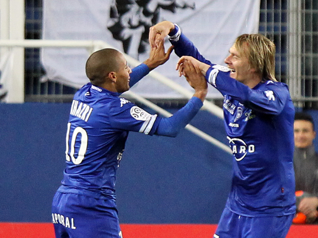 Bastia's Serbian midfielder Milos Krasic is congratulated by Tunisian midfielder Wahbi Khazri after he scored a goal during a French L1 football match against Evian in the Armand Cesari stadium in Bastia on December 1, 2013