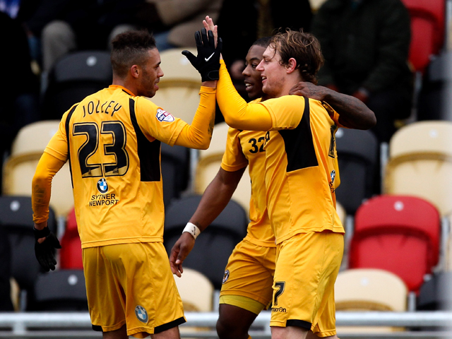 Adam Chapman of Newport celebrates with team mates after scoring his team's second goal of the game during the Sky Bet League Two match between Newport County AFC and Chesterfield at Rodney Parade on December 01, 2013